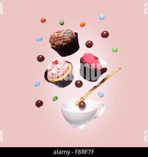 Cupcakes and candy mid air - Stock Photo