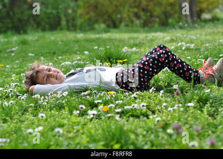 Girl lying on grass in springtime - Stock Photo