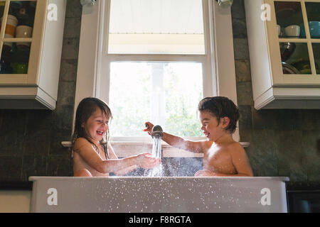 Young boy and girl sitting in kitchen sink playing with water - Stock Photo