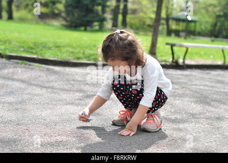 Girl drawing hopscotch on road with chalk - Stock Photo