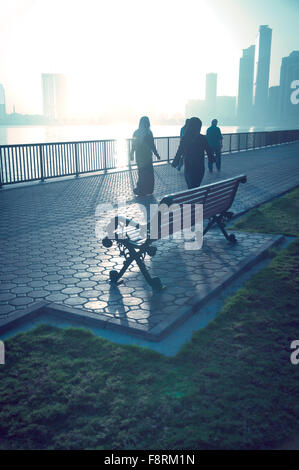 Arab woman taking a walk early in the morning in winter on the corniche. - Stock Photo