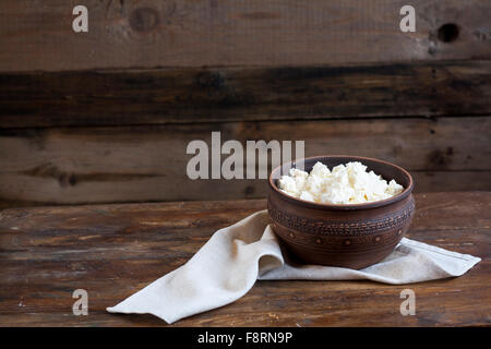Culinary cottage cheese in a clay bowl on dark wooden table - Stock Photo
