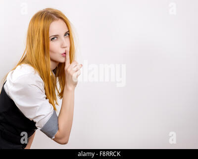 Young Woman Shows Silence Sign In white Background with copyspace - Stock Photo