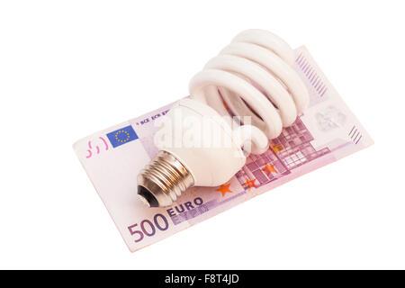 Enegy saver bulb over 500 euro bills on white background - Stock Photo