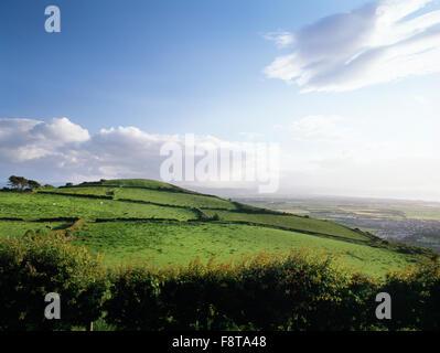 Bronze Age round barrow & site of a Neolithic settlement on summit of Bryn Llwyn hillside, looking SW from Gwaenysgor - Stock Photo