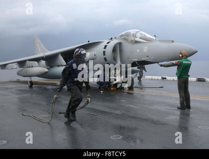 Sailors remove chocks and chains from an Italian AV-8B Harrier aboard the amphibious assault ship USS Kearsarge - Stock Photo