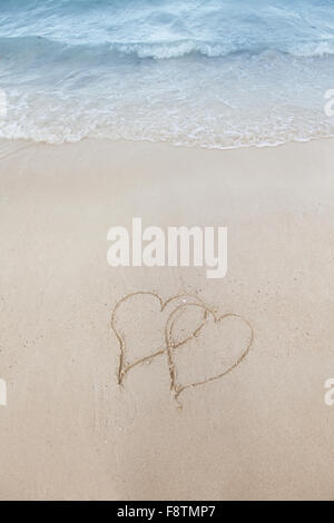 Love on beach concept - two hearts on a beach sand with coming wave - Stock Photo