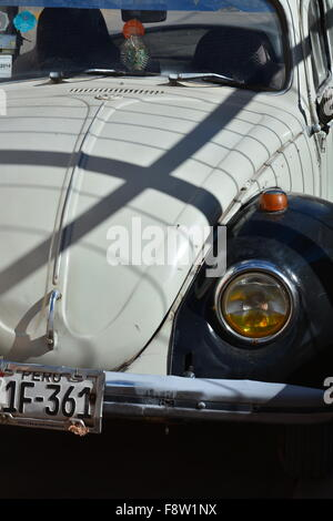 An old black and white VW Bug on the streets of Urubamba Peru. - Stock Photo