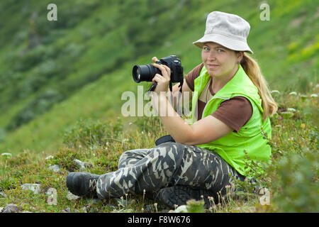 photographer tourist takes pictures nature at mountains - Stock Photo