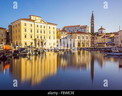 Buildings on the Main Square Tartini of Piran City Reflected on Water in Slovenia. - Stock Photo