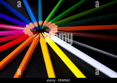 Brightly colored pencil crayons from the red side of the colour spectrum are arranged into a circle or wheel making - Stock Photo