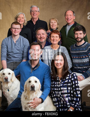 Studio portrait of family including three sisters, spouses & grown children & two Platinum colored Golden Retriever - Stock Photo