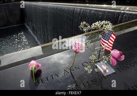 US flags, flowers and victim's photography left on the names on the National September 11 Memorial. New York City - Stock Photo