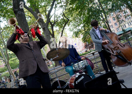 A musician playing two trumpets at same time during a performance in Washington Square Park Greenwich Village, New - Stock Photo