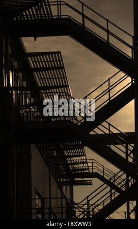 Silhouette of outside fire escapes on a modern building at dusk - Stock Photo