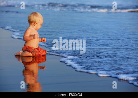 On sunset beach funny baby sit on black wet sand and crawling to sea surf for swimming in waves. - Stock Photo