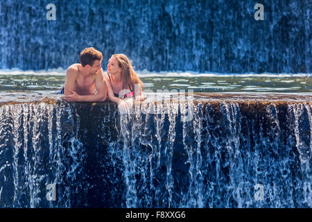 Happy family on honeymoon holidays - just married loving couple swimming with fun in waterfall natural pool. - Stock Photo