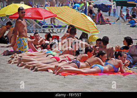 Row of young women sunbathing on beach, Fuengirola, Costa del Sol, Malaga Province, Andalucia, Spain, Western Europe. - Stock Photo