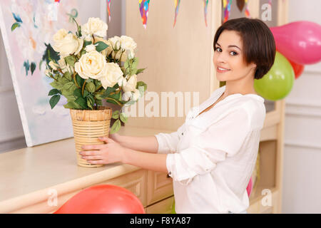 Young girl decorating her apartment for birthday party - Stock Photo