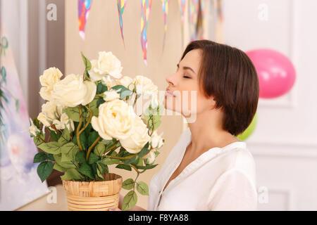 Young lady is smelling the flowers - Stock Photo