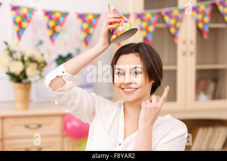 Young smiling girl tries on her party hat - Stock Photo