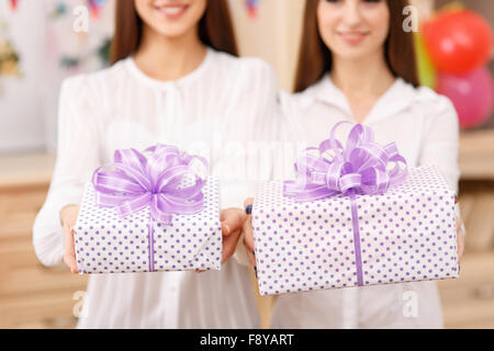 Two young ladies holding presents. - Stock Photo