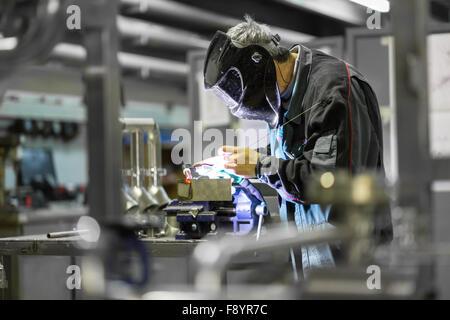 Industrial worker welding in metal factory. - Stock Photo
