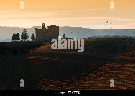 View the sunset over the hills of the Castle of Grinzane Cavour Unesco heritage in the territory of the Langhe Piedmont - Stock Photo