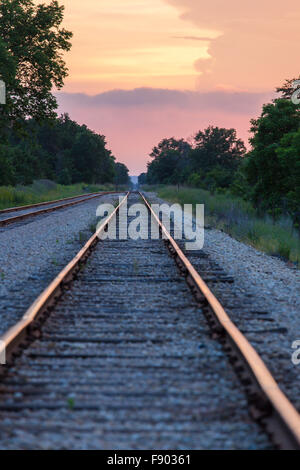 Long straight railroad tracks running into the distance at sunset with warm colors in sky and reflecting on tracks - Stock Photo