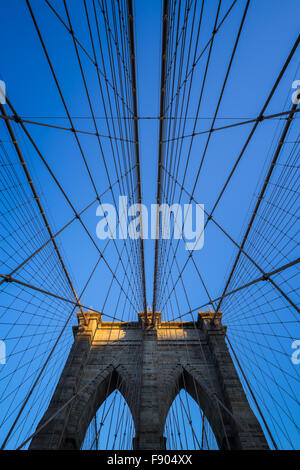 Brooklyn Bridge tower with double gothic arches and symmetrical suspension cables at sunset with clear blue sky, - Stock Photo