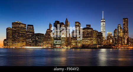 New York City skyline of Lower Manhattan Financial District at twilight with  illuminated skyscrapers rising above - Stock Photo