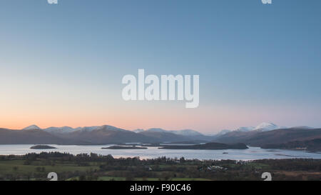 Loch Lomond winter sunset,  with the snow capped peak of Ben Lomond on the right. - Stock Photo