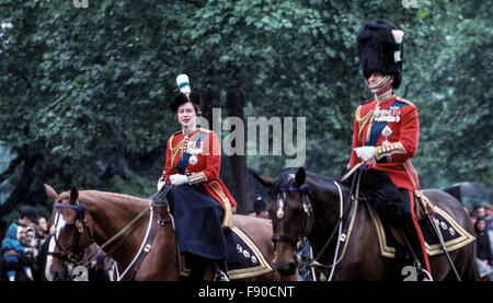 A young Queen Elizabeth II and Prince Philip ride their horses from Buckingham Palace along the street in June, - Stock Photo