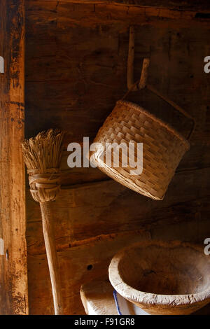 Log cabin interior with a homemade broom, basket, and wooden kneading bowl at the Museum of Appalachia, Tennessee, - Stock Photo