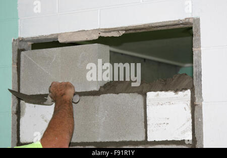 closing a door way with concrete blocks - Stock Photo