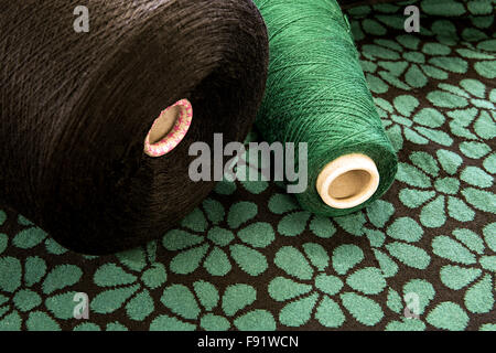 Textile Still Life - Close Up of Large Spools of Brown and Green Thread on Floral Patterned Background with Copy - Stock Photo