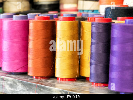 Textile Still Life - Close Up of Industrial Size Spools of Cotton Thread in Vibrant Colors of Pink, Orange, Yellow - Stock Photo