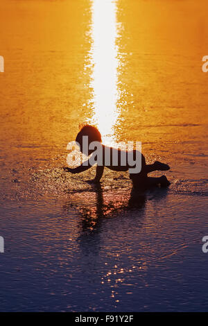 Black shadow silhouette of playful baby running on wet gold sunset sand to sea surf to swim in beach wave. - Stock Photo