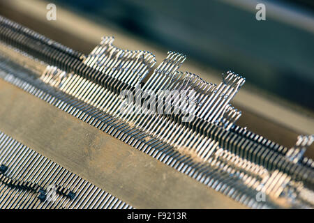 Needles closeup of a knitting machine in a knitwear factory - Stock Photo