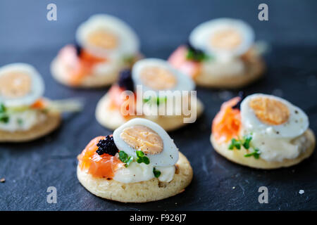 Party food, blinis with salmon, quail egg and caviar - Stock Photo