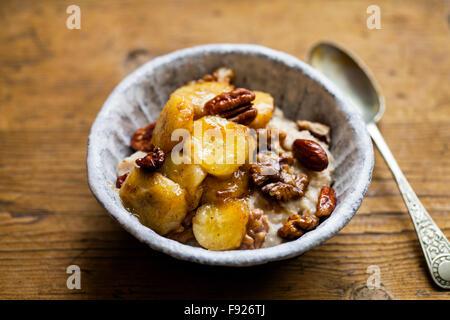 Porridge with caramelized banana and nuts - Stock Photo