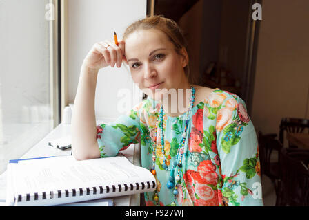 Young woman studying in the cafe - Stock Photo