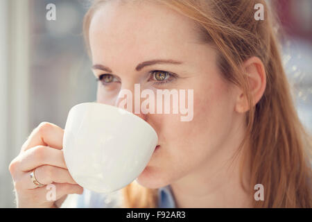 Woman drinking coffee - Stock Photo