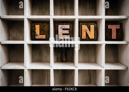 The word 'LENT' written in vintage ink stained wooden letterpress type in a partitioned printer's drawer. - Stock Photo
