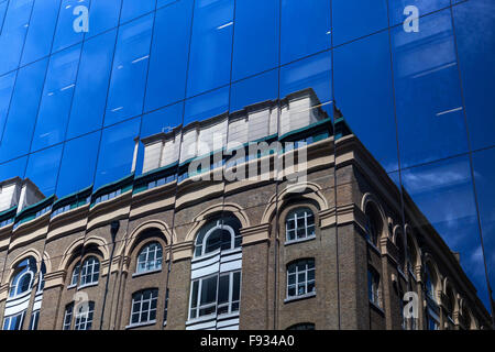 Reflections of old building and blue sky reflected in the glass frontage of a modern office block in London, England, - Stock Photo