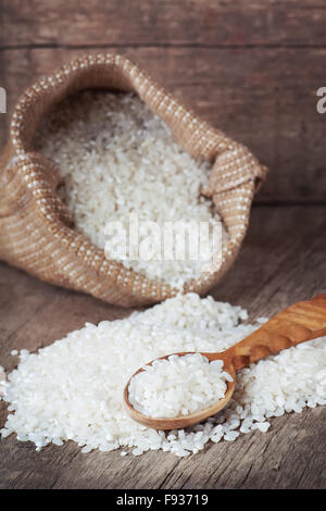 White rice on the wooden spoon and in the sack bag on old wooden background - Stock Photo