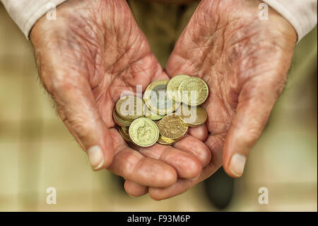 Shiny gold pound coins held out in hands showing all small savings and money plea for help poverty stricken pensioner - Stock Photo