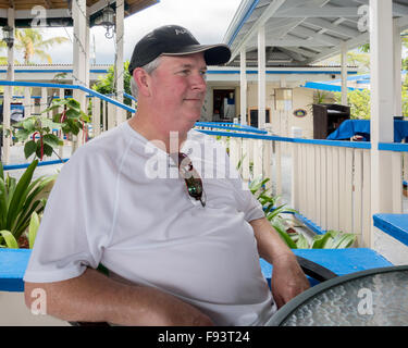 A 50 year old obese Caucasian man sitting at a open air table in a beachside cafe in St. Croix, U.S. Virgin Islands. - Stock Photo