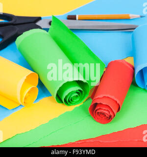 still life - scissor, pencil and rolled color paper on sheets of plain paper - Stock Photo