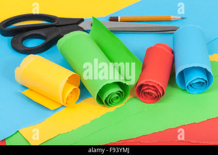 still life - creative material from rolled color paper on sheets of torn paper - Stock Photo